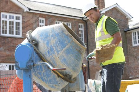 empleadas domesticas: Cemento de mezcla de trabajadores de construcción  Foto de archivo