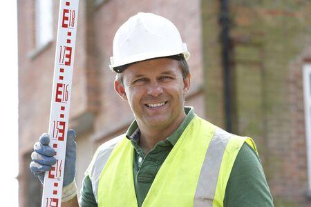 encuestando: Medida de holding de trabajadores de construcción  Foto de archivo