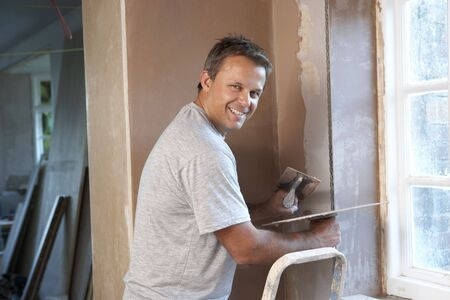 Plasterer Working On Interior Wall photo