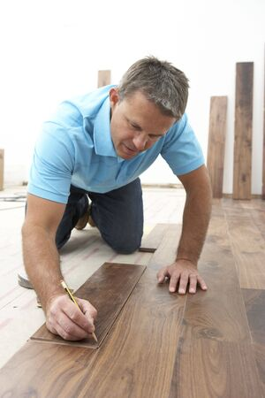 lying on the floor: Builder Laying Wooden Flooring