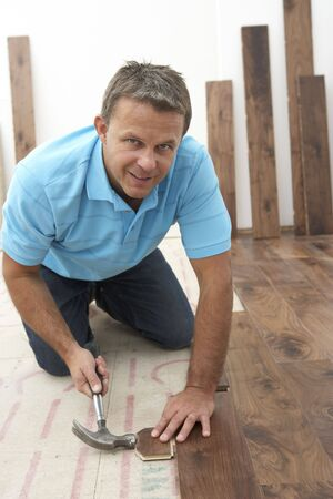Builder Laying Wooden Flooring photo