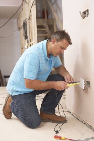 electric socket: Electrician Installing Wall Socket Stock Photo