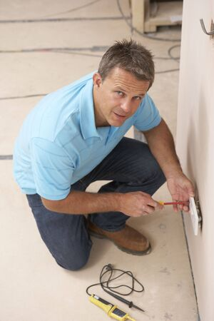 middle aged men: Electrician Installing Wall Socket Stock Photo