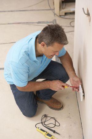 Electrician Installing Wall Socket photo