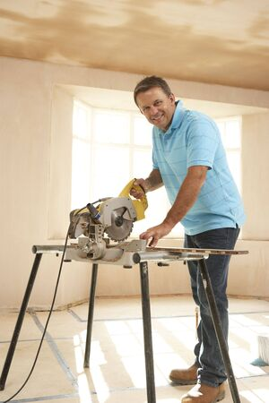 electric saw: Builder Using Electric Saw Stock Photo