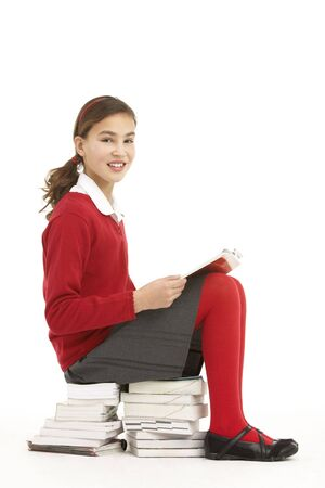 Female Student In Uniform Sitting On Pile Of Books Reading Stock Photo - 6456672