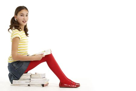 11 year old girl: Young Girl Sitting On Pile Of Books Reading