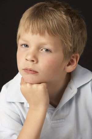 6 year old: Studio Portrait Of Thoughtful Young Boy Stock Photo