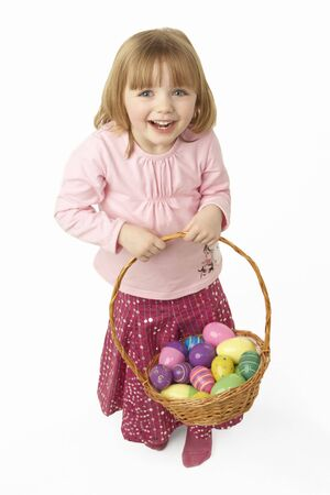 Young Girl Carrying Basket Filled With Easter Eggs photo