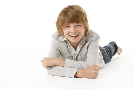 boy 12 year old: Young Boy Lying On Stomach In Studio Stock Photo