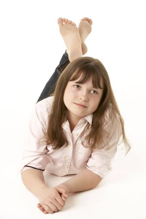 Thoughtful Young Girl Lying On Stomach In Studio photo