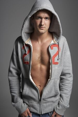 Studio Portrait Of Sexy Young Man Wearing Hooded Sweat Top photo