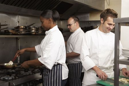 apprentice: Team Of Chefs Preparing Food In Restaurant Kitchen