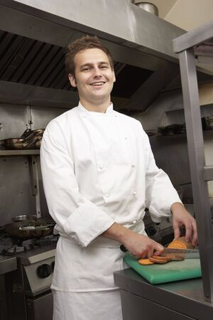 chefs whites: Male Chef Preparing Vegetables In Restaurant Kitchen