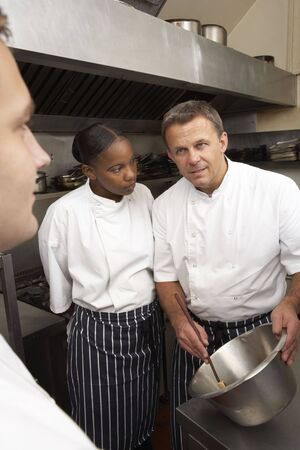 instructing: Chef Instructing Trainees In Restaurant Kitchen Stock Photo