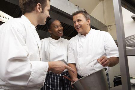 Chef Instructing Trainees In Restaurant Kitchen photo