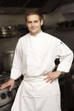 Male Chef Standing Next To Cooker In Restaurant Kitchen photo