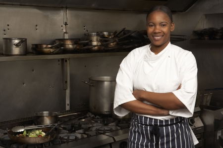 apprenti: Femelle chef permanent suite � la cuisini�re � la cuisine du restaurant Banque d'images
