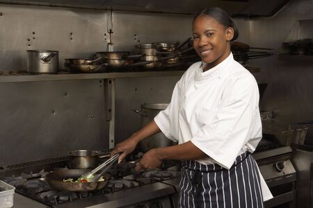 Female Chef Preparing Meal On Cooker In Restaurant Kitchen photo