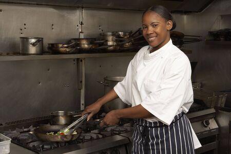 chefs whites: Female Chef Preparing Meal On Cooker In Restaurant Kitchen Stock Photo