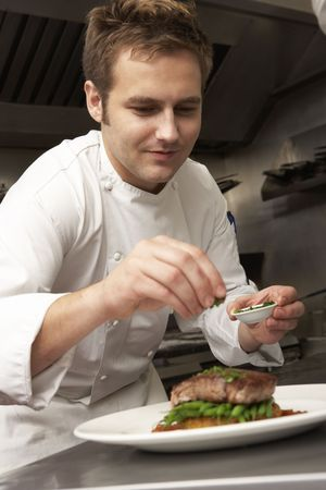Chef Adding Seasoning To Dish In Restaurant Kitchen photo