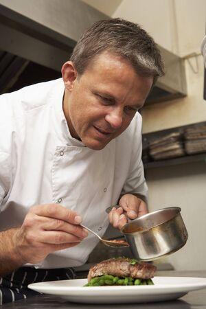 hombre cocinando: Chef agregar salsa al plato de la cocina del restaurante