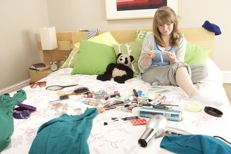 messy clothes: Teenage Girl In Untidy Bedroom Waxing Legs