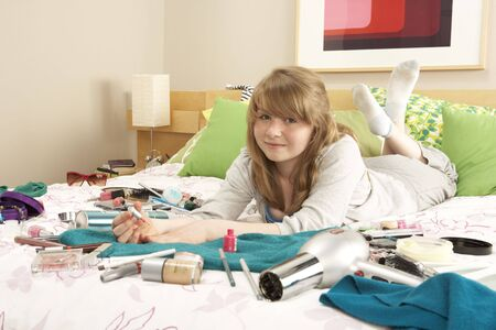 Teenage Girl In Untidy Bedroom Painting Nails photo
