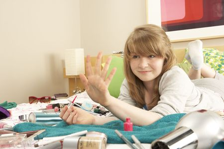 Teenage Girl In Untidy Bedroom Painting Nails Stock Photo - 6450899
