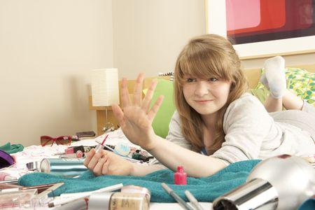 untidy: Teenage Girl In Untidy Bedroom Painting Nails