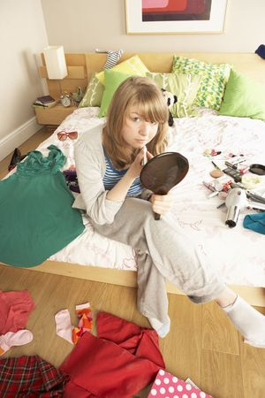 Teenage Girl Putting On Make Up In Untidy Bedroom photo