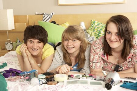 Group Of Teenage Girls In Untidy Bedroom photo