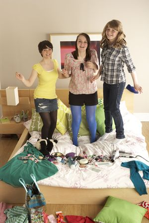 messy clothes: Group Of Teenage Girls Hanging Out In Untidy Bedroom Stock Photo
