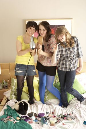 Group Of Teenage Girls Hanging Out In Untidy Bedroom photo