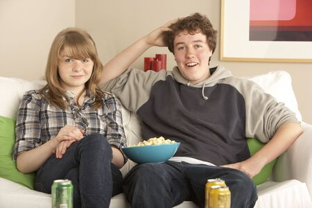 Teenage Couple Sitting On Sofa Watching TV photo