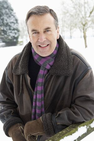 Senior Man Standing Outside In Snowy Landscape photo