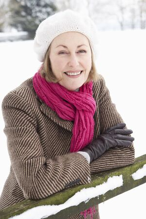 Senior Woman Standing Outside In Snowy Landscape photo
