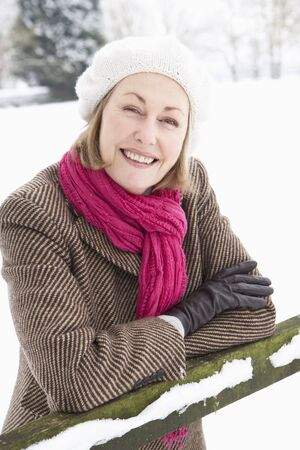 Senior Woman Standing Outside In Snowy Landscape photo