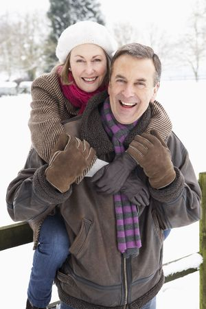 couple cuddling: Senior Couple Standing Outside In Snowy Landscape