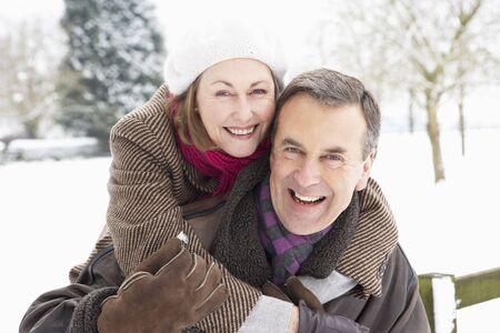 senioren wandelen: Senior Couple permanent buiten In Snowy liggend