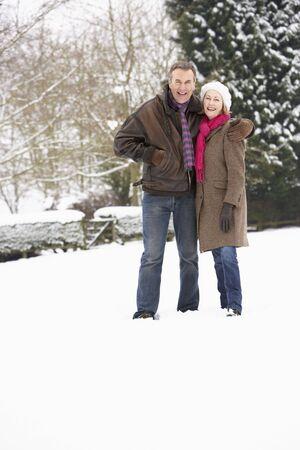 Senior Couple Walking In Snowy Landscape photo