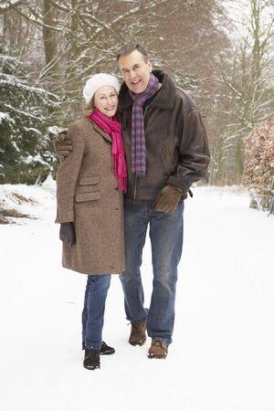 Senior Couple Walking Through Snowy Woodland photo