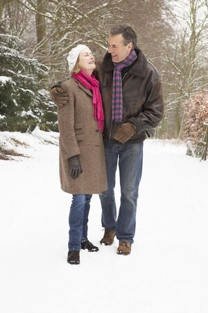 countryside loving: Senior Couple Walking Through Snowy Woodland