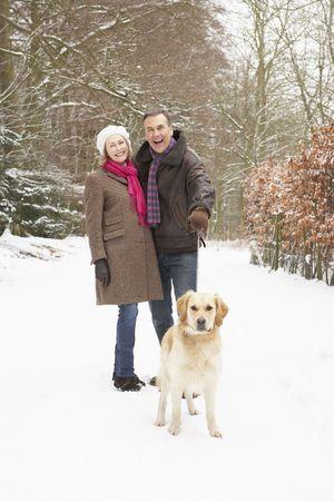Senior Couple Walking Dog Through Snowy Woodland Stock Photo - 6451359