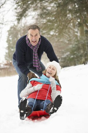 sledging: Senior Couple slitta attraverso il bosco innevato