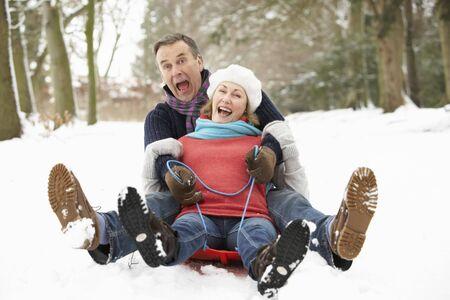 Senior Couple Sledging Through Snowy Woodland photo