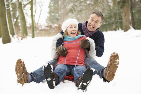 having fun in the snow: Senior Couple Sledging Through Snowy Woodland