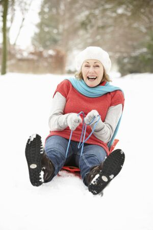 Senior Woman Sledging Through Snowy Woodland Stock Photo - 6451025