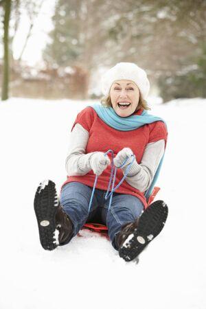 Senior Woman Sledging Through Snowy Woodland Stock Photo - 6451025
