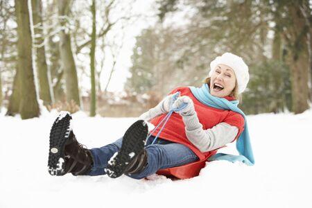 sledging: Senior Woman slitta attraverso il bosco innevato  Archivio Fotografico